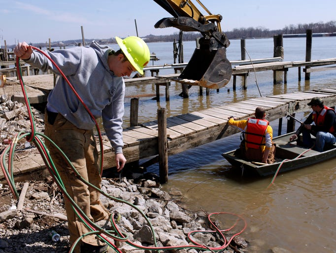 Jeffersonville Parks Department employees from left, Morgenn Evans, Tyler Rhodes and John Smedal work on removing the top portion of one of the 27 boat docks to be removed at the downtown Jeffersonville wharf. The decades-old, inclusive downtown river community has been cleared in recent months in preparation for Mayor Mike MooreÕs $2.2 million marina proposal.  March 20, 2014