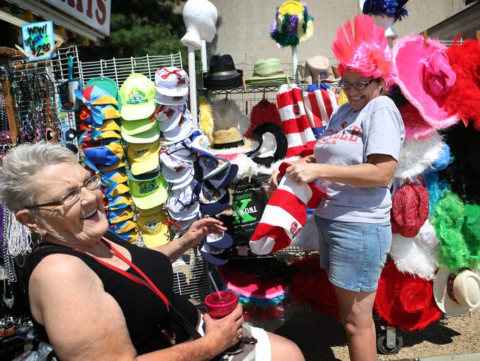 Glenda Bowen, left, laughs as her daughter Dottie Ferguson, both of Georgetown, Ind., tries on a pink mohawk at the Kentucky State Fair in Louisville on the first day of the fair. This was Bowen's first time at the fair. Aug. 14, 2014.