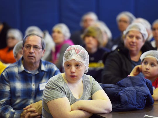 Ally O'Brien , 23, (C) and other volunteers listen during an orientation for packing more than 150,000 meals  that will be shipped to NJ Community Food Bank as well as to northern Haiti, hosted by Grains of Hope during the 7th annual food packing event at the Pequannock Township Middle School in Pequannock on March 19th, 2017.