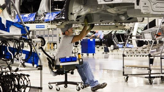 An employee works on a Passat sedan at the Volkswagen plant in Chattanooga, Tenn., where the company has adopted a new labor policy