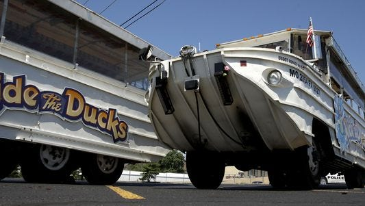 A man looks at an idled duck boat in the parking lot of Ride the Ducks in Branson, Mo.