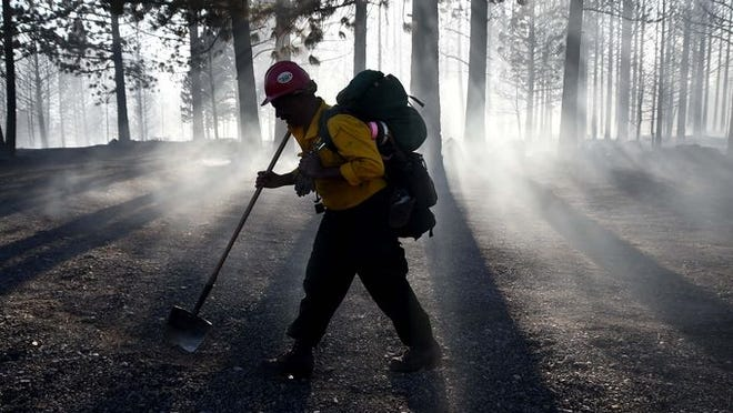 A firefighter walks through the smoke of a burned forest near Boca Reservoir on Monday afternoon. Calm winds and a close water supply at Boca for the helicopters fighting the blaze kept the fire from being worse. Four air tankers, including a jet tanker, were also instrumental in keeping the fire contained.