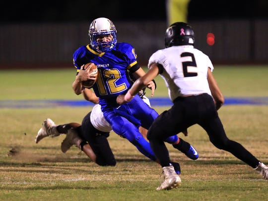 Odem's Michael Everett (12) dodges Hebbronville's Zach Trevino en route to a first down Friday night. Everett threw five touchdown passes and ran for two more int he 51-21 win.