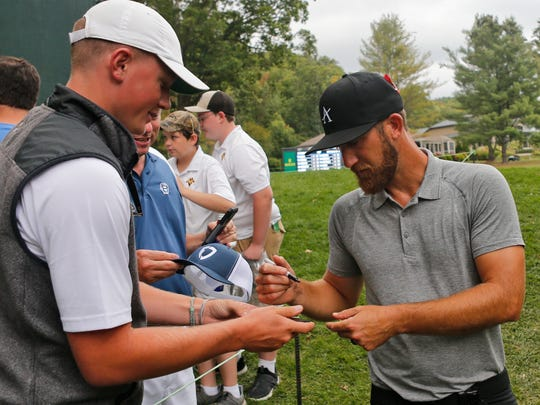 Kevin Chappell, right, gives autographs to fans after the ninth hole during the second round of A Military Tribute at The Greenbrier golf tournament in White Sulphur Springs, W.Va., Friday, Sept. 13, 2019. (AP Photo/Steve Helber)