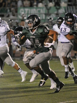 Dinuba's Michael Wright runs the ball against Mission Oak on Friday night in Dinuba.