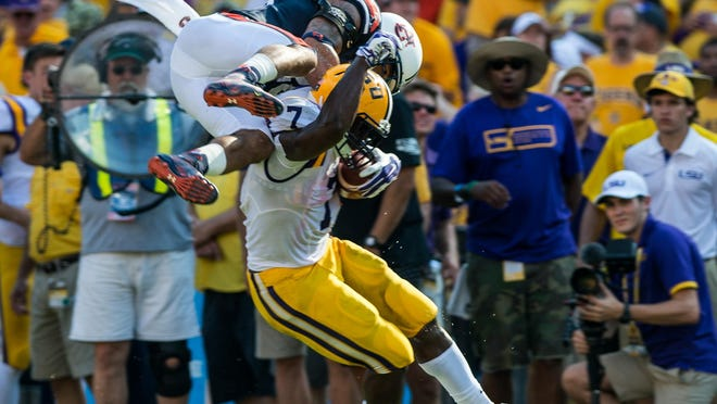 LSU Tigers running back Leonard Fournette (7) avoids a flying tackle by Auburn Tigers defensive back Tray Matthews (28) on a 29-yard touchdown run during the second half of NCAA football game at Tiger Stadium in Baton Rouge, La., Saturday, Sept. 19, 2015.