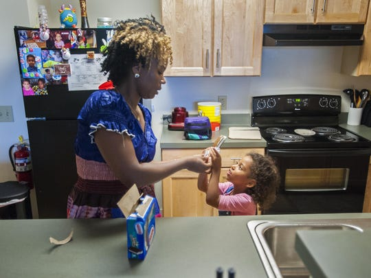 Alicia Araje, an immigrant from Burundi, shares ice cream with her daughter Alison at their new Burlington apartment, provided by Champlain Housing Trust.