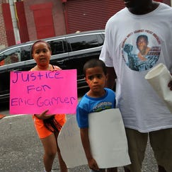 Emerald Garner, right, stands next to the coffin of her father, Eric Garner, during his funeral at Bethel Baptist Church in the Brooklyn borough of New York on Wednesday, July 23, 2014. Garner died in police custody after an officer placed him in an apparent chokehold.