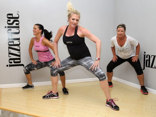 Katie Woody, center, teaches a Jazzercise Fusion class with assistance from Kim Benson, left, and Nancy Mills at the E. Chestnut Exp. location on Tuesday, July 15, 2014.