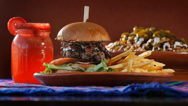 The Border Burger at Kahlo Kitchen features a thick beef patty, asadero and manchego cheese mix, lettuce, tomato, pickles, caramelized onions, a hot dog, ham, bacon, avocado and Kahlo's special sauce topped off with a mild salsa, all with a side of fries. Try it with a strawberry lemonade and a plate of hearty nachos.