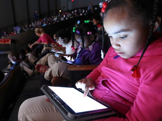 Adrionna Walker, a student at Engelhard Elementary, uses a tablet to create art that was shown on a screen as part of Stage One's production of Harold and the Purple Crayon at the Kentucky Center.