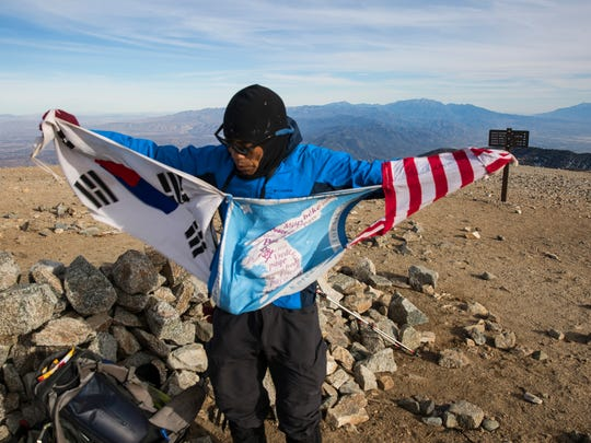 Sam Kim unfurls flags on the summit of Mt. Baldy, the highest point in the San Gabriel Mountains at 10,064 feet. (Brian van der Brug/Los Angeles Times/TNS)