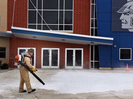 Brad Hepfer clears snow off the sidewalk Monday, Feb. 15, 2016 at Chambersburg Area Senior High School. Districts school are out because of the overnight storm that left roads slick in the area.