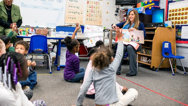 Citizen-Times reporter Beth Walton teaches a kindergarten class at Hall Fletcher Elementary School in West Asheville in November. She was volunteering to teach with Junior Achievement, a nonprofit that teaches financial literacy.
