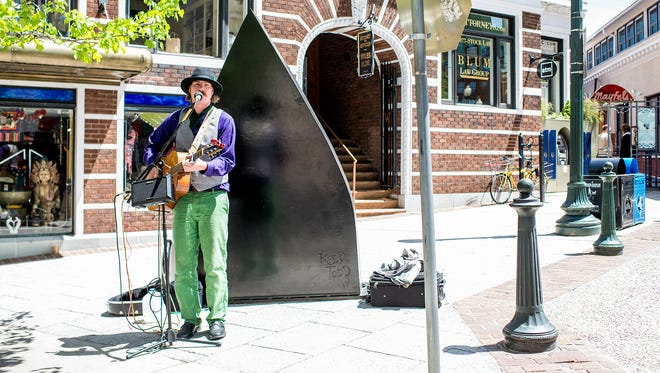 Mick Mullen sings and plays guitar next to the Flat Iron Building in downtown Asheville in this file photo. The city of Asheville does have a guide for buskers, create in conjunction with local street performers.