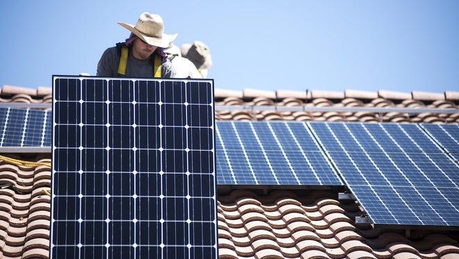James Hewitt prepares to hand Joe Segundo and Benjamin Jennings a solar panel during an installation in Buckeye.