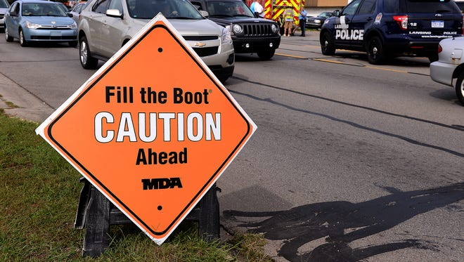 """A double-sided sign on the side of the road warns drivers that firefighters are out collecting donations for the """"Fill the Boot"""" campaign, Wednesday, Sept. 9, 2015 in Lansing, Mich. Dennis Rodeman, a 35-year-old Lansing firefighter has died after being struck by a hit-and-run driver as he collected money for charity."""