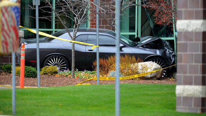 A car sits idle after ramming into the Mid-Michigan Physicians building  Wednesday, November 18, 2015, in Lansing Township.