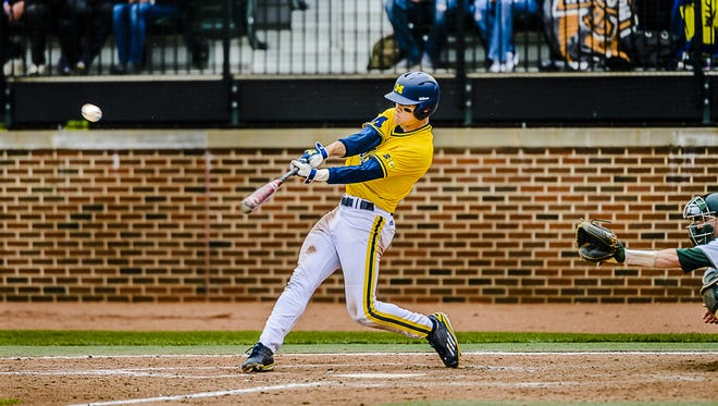 Lakeview High School graduate Jake Bivens of Michigan hits a double against Michigan State ion April 30, 2016 in East Lansing.