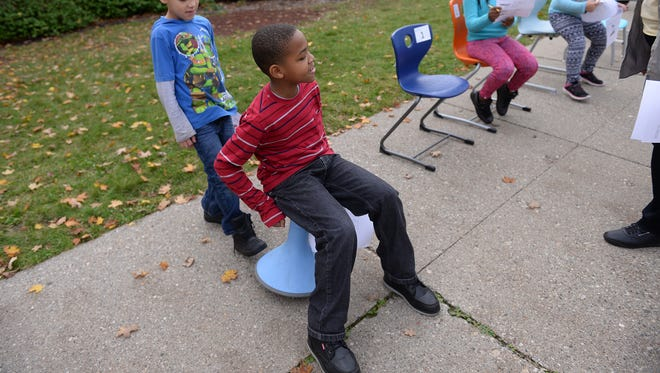 Third grader Tre'Vaughn Henry tries out some furniture in front of Reo Elementary on Thursday, Nov. 3, 2016 during the Pathway Promise Furniture Bus Tour in Lansing. Voters in the Lansing School District approved a $120 million millage for school improvements and upgrades in May. The bus tour was designed to allow students an opportunity to try out and provide input on new furniture.