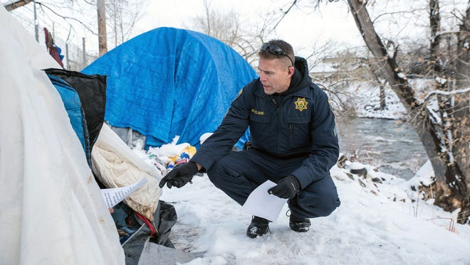 Reno Police Sgt. Wade Clark makes contact with people living in tents along the Truckee River Jan. 7, 2017 before a forecasted flood.