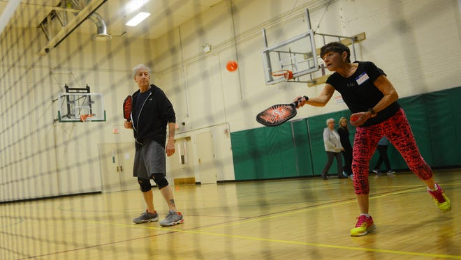 Stephen Katz and Sandy McBride warm up on Tuesday, Feb. 7, 2017 during the intermediate level class of pickleball at the Hannah Community Center in East Lansing. Katz used to play racquetball when he was younger and said pickleball has been a great way to still stay active.