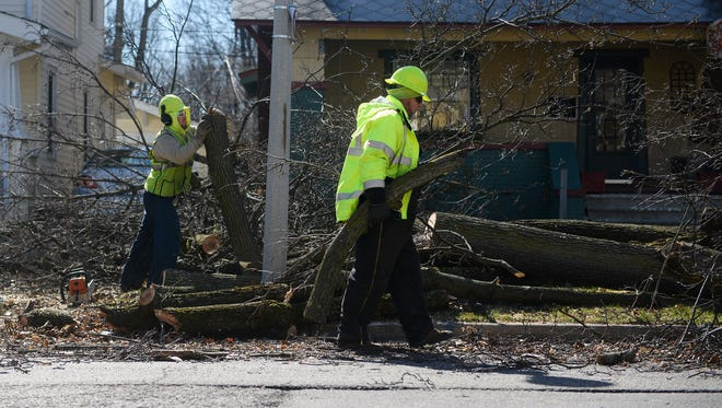 Crews work to remove a tree that fell due to high winds on Wednesday, March 8, 2017 in front of a home on Shiawassee Street in Lansing.
