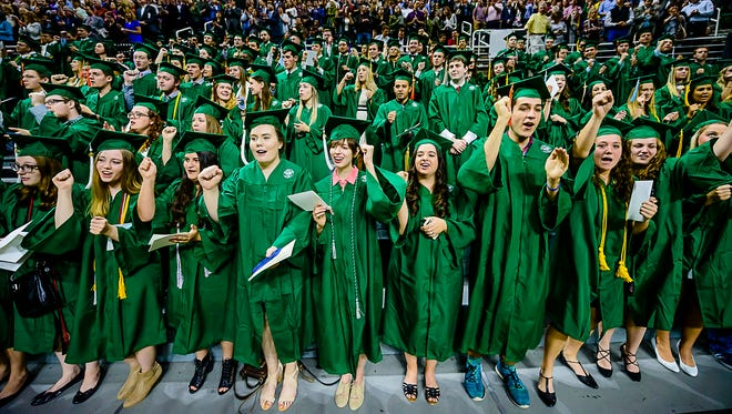 Graduates sing the MSU Fight song at Kirk Gibsons' impetus during MSU spring commencement at the Breslin Center in May of 2017.