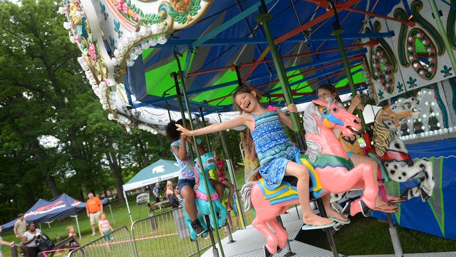 Noel Schinkel rides a carousel on Friday, June 16, 2017 at Lake Lansing Park South in Haslett. The carousel returned to the park as part of Meridian Township's 175th anniversary celebration.