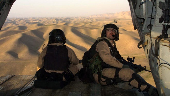 U.S. special operations soldiers keep watch from a U.S. Army Special Forces Chinook helicopter near Khwaja Bahuaddin, Afghanistan, in this Nov. 15, 2001 file photo.