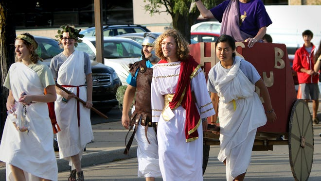 Members of the Homestead High School Latin Club pull a chariot south on Cedarburg Road during the school's Homecoming parade in 2015.This year's homecoming festivities are planned for Oct. 2-7.