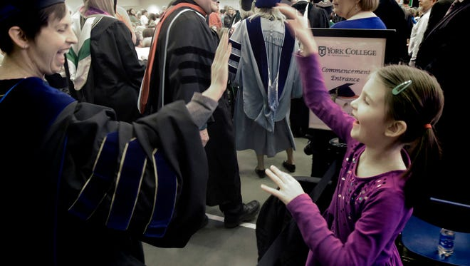 Bridgette Hagerty high fives her daughter, Abby Warner, 6, as Hagerty entered the York College Winter Commencement Wednesday, Dec. 20, 2017. Hagerty, a biology professor, was one of the commencement speakers. They live in Spring Garden Township. The ceremony graduated nearly 300 students at Grumbacher Sport & Fitness Center. Bill Kalina photo