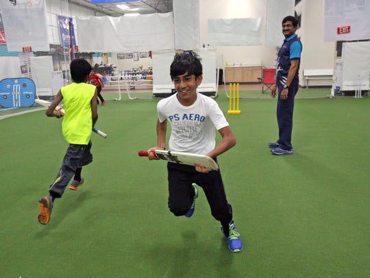 Students learn the game of cricket at CricMax. Head coach Ashok Patel, right, watches as Kunal Pilla,10, of Monmouth Junction, left, and Ram Patel,12, of North Brunswick, run the bases. CricMax is one of two local indoor cricket facilities that allow for year-round training and practice.
