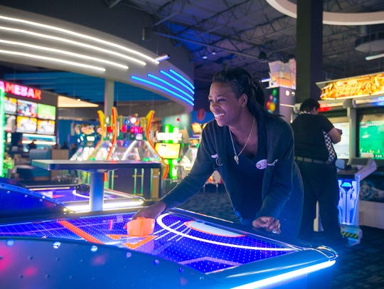 Employee Candice Marshall plays an arcade game at the