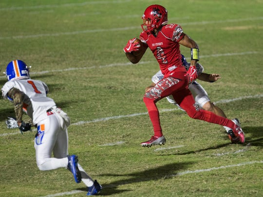 North Fort Myers High School's Joe Wilkins Jr. breaks free from Cape Coral defenders during first quarter play recently at North Fort Myers High School. North beat Cape 41-0.