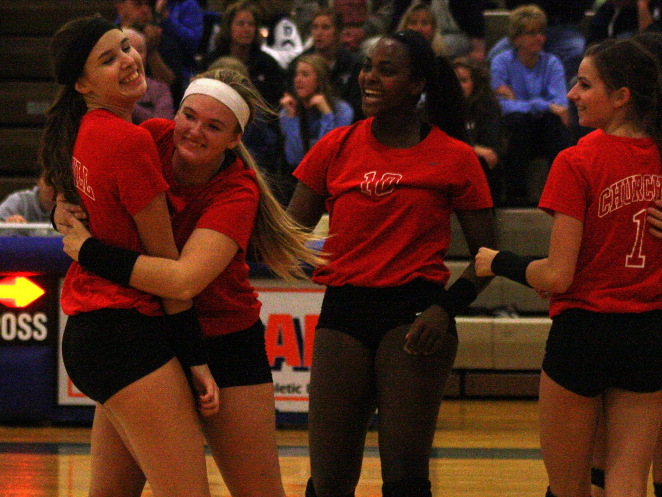 Livonia Churchill volleyball players celebrate a big point during Wednesday's match against Stevenson.