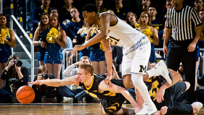 Iowa guard Mike Gesell, bottom, reaches for the loose ball, competing with Michigan guard Zak Irvin, top, in the first half Saturday.