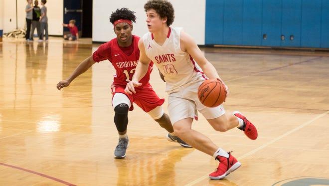 St. Clair's Ben Davidson (13) dribbles the ball around Lake Shore High School's Omari Ruffin during their basketball game at St. Clair High School Feb. 20.