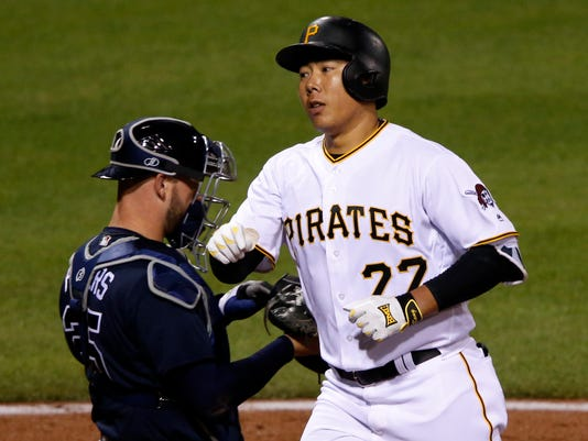 Pittsburgh Pirates' Jung Ho Kang (27) crosses home plate past Atlanta Braves catcher Tyler Flowers after hitting a solo home run off Arodys Vizcaino during the ninth inning of a baseball game in Pittsburgh, Wednesday, May 18, 2016. The Braves won 3-1. (AP Photo/Gene J. Puskar)