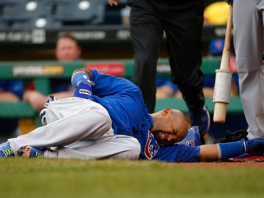 Chicago Cubs' Emilio Bonifacio lies on the ground after collapsing coming out if the batter's box during the first inning of a baseball game against the Pittsburgh Pirates in Pittsburgh, Thursday, June 12, 2014. Bonifacio was helped to the dugout and left the game. The nature of his injury was not known at the time. (AP Photo/Gene J. Puskar)