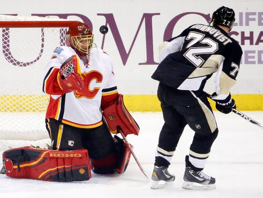 Calgary Flames goalie Jonas Hiller (1) stops a shot by Pittsburgh Penguins' Patric Hornqvist (72) during the first period of an NHL hockey game in Pittsburgh Friday, Dec. 12, 2014. (AP Photo/Gene J. Puskar)