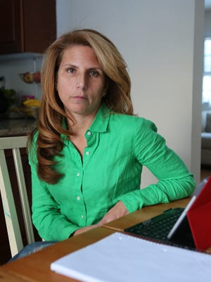 Teacher Carin Mehler was reassigned to work from home by the Rye school district. She is shown in the dining area of her Rye home Jan. 7, where she uses a tablet to work on lesson plans. She says the district is yet to bring charges against her, and district taxpayers are paying her full salary and benefits to keep her at home.