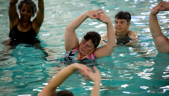 Women stretch during their morning water aerobics class