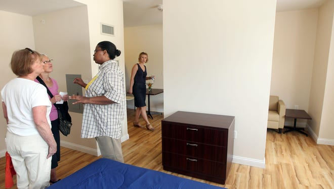 "Rhonda Clairborne (foreground right), a resident of Anna Louise Inn, downtown, talks with Mary Hattemer, of Mount Lookout and Charlotte Brooks, of Hyde Park, in one of the 85 efficiency apartments in the new Anna Louise Inn, Mount Auburn. Claiborne has lived at the Anna Louise Inn Downtown for five years and will be moving to the new facility. ""I'm overwhelmed,"" she said, ""I love it."""