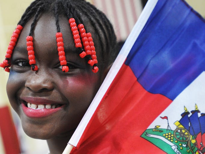 Imane Abdou-Saleye, 7, holds a Haitian flag at the festival. A Haitian Flag Day celebration was held at St. Michael the Archangel Church Sunday May 18, 2014.