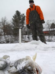In this 2006 file photo, Adam Toboyek, of Mosinee stands near his fishing hole Saturday during the Mosinee Ice Fishing Jamboree.  At the time of the photo his walleye was holding the top spot, while also holding the third spot with a crappie.  He and his friends had totaled 14 fish up to that point.