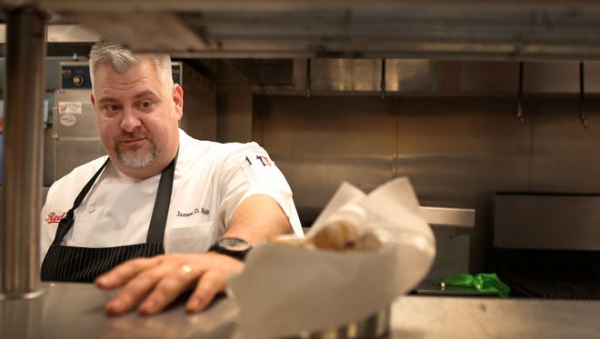 """Great American Ball Park Executive Chef James Major prepares a dessert in the Diamond Club Kitchen at GABP. Major won the ballpark-themed """"Chopped"""" competition on the Food Network last fall."""