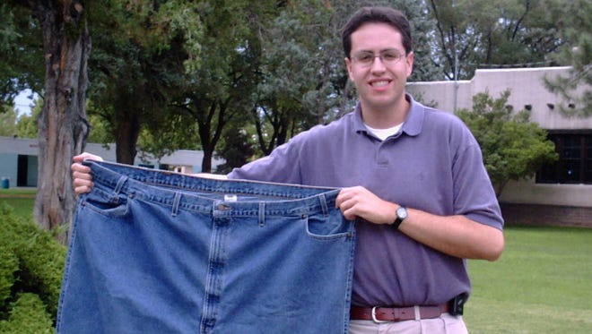 Jared Fogle holds up a pair of jeans he used to wear after losing weight in Albuquerque, N.M. on Aug. 7, 2001.