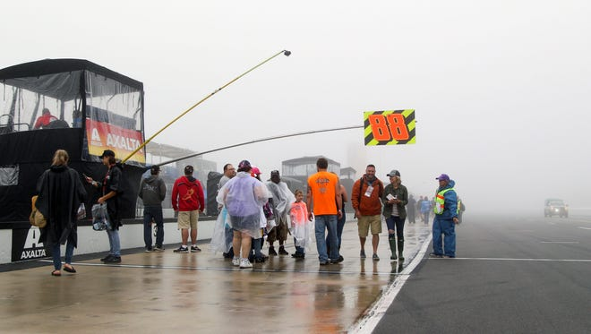 Fans walk on pit road at Pocono Raceway on Sunday, surrounded by mist and fog. (Matthew O'Haren, USA TODAY Sports)