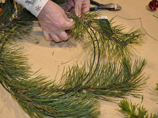 To get started making a wreath, place greenery around a frame and wind wire in a clockwise direction.